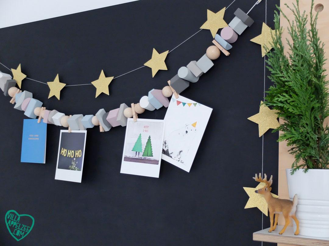 Kaartjes-slinger van geverfde speelgoedblokjes tegen zwart schoolbord.