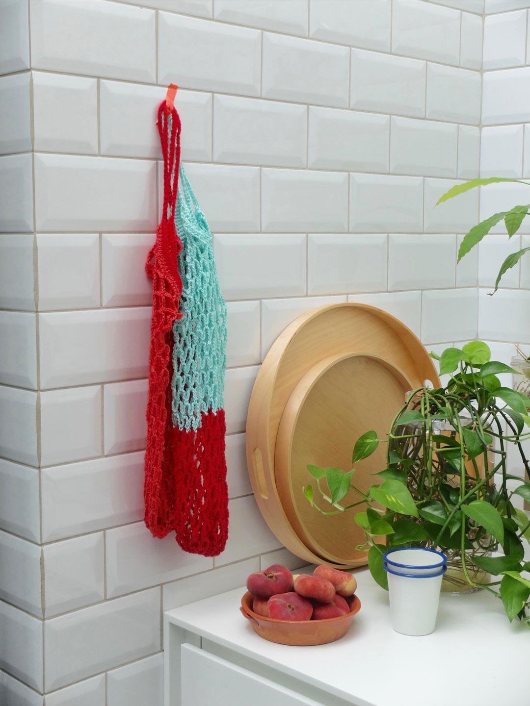 Roze en blauw/rood gehaakt boodschappennetje met tape bevestigd aan witte keukenmuur - Villa Appelzee
