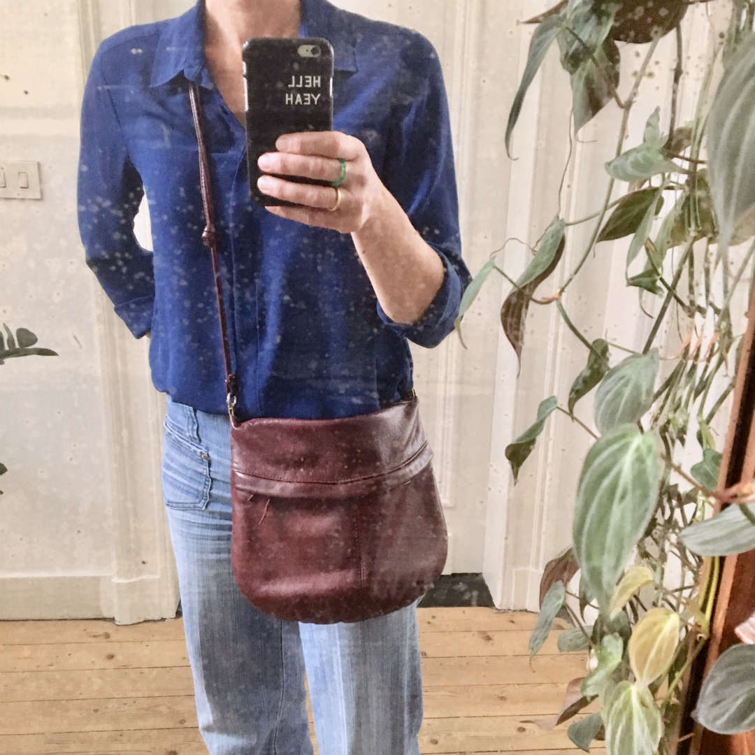 Selfie in mirror with blue second hand blouse and dark red purse