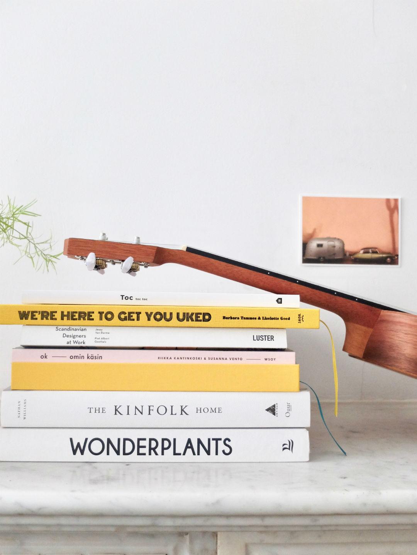 Stapel boeken en ukelele op marmeren schouw