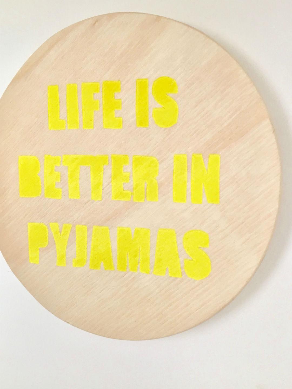 Houten schijf met quote in gele letters