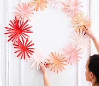 Krans van papier in roze tinten tegen witte muur. Foto: Wout Hendrickx.