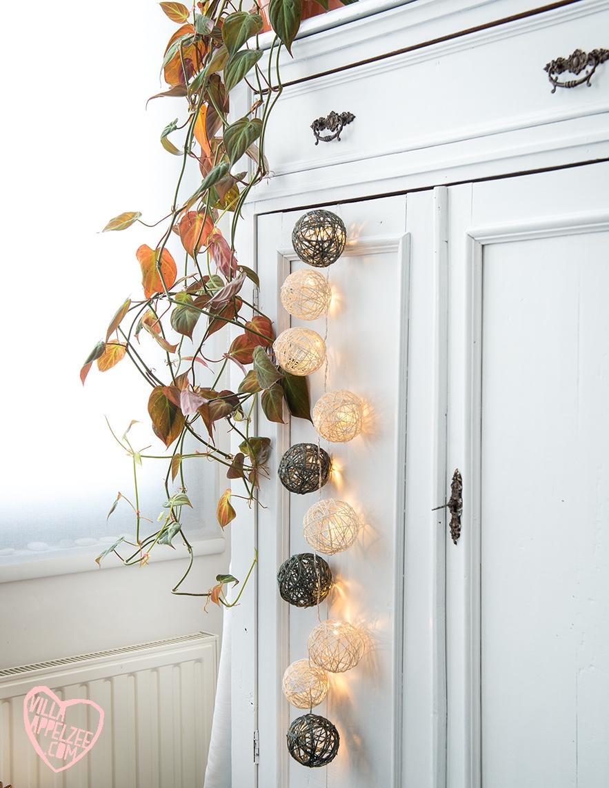 DIY lichtjesslinger met balletjes in touw, tegen witte kast met hangplant, appelzee.com. Foto: Karel Daems.