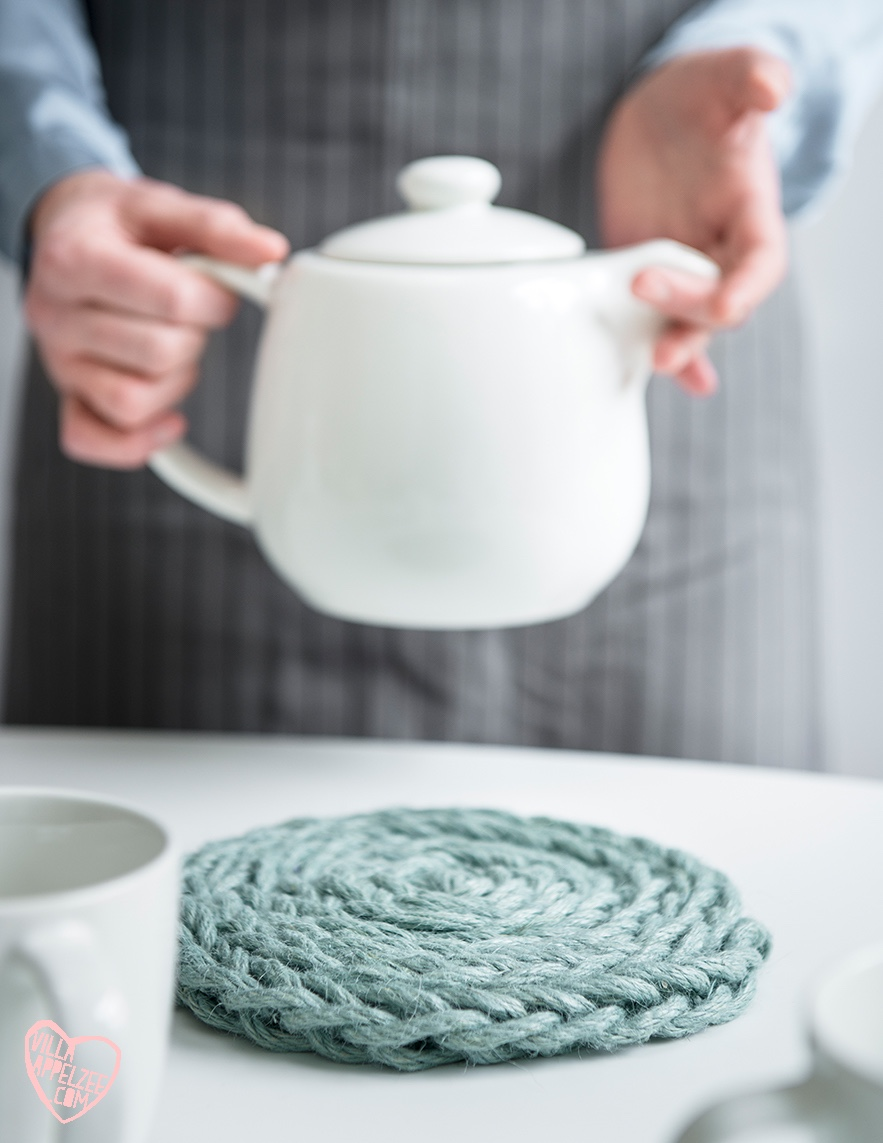 DIY gehaakte onderzetter in grijs touw op tafel met witte theepot, appelzee.com. Foto: Karel Daems